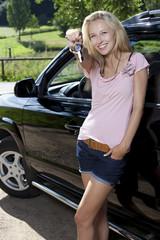 junge frau zeigt autoschlüssel
