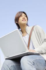 屋外でノートパソコンを使う大学生