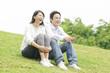 芝生に並んで座るカップル
