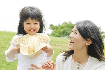 麦わら帽子を持った女の子と母親
