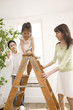 脚立に登る女の子と見守る両親