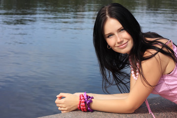 Dark-haired girl in pink sleeveless shirt against pond