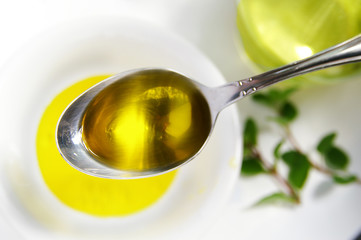 spoon full of love oil, over herbs and bowl