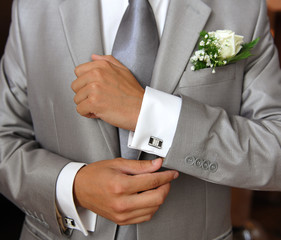 Groom in grey suit ficing his cufflink