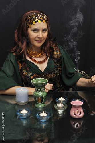 Smiling woman at ritual actions on a black background