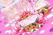 Pink birthday party cupcake with ribbons and gifts.
