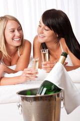 Two women toasting with champagne in bedroom
