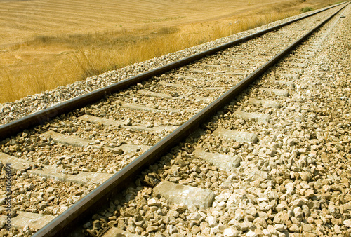 Railroad tracks curving off into the rural fields
