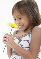 A happy, smiling child holds a single yellow flower.