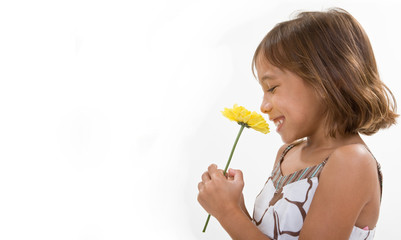 A smiling child holds a single yellow flower