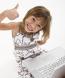 A young girl playing on a laptop
