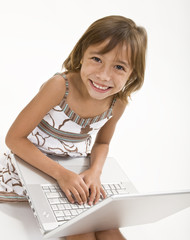 A young girl working on a laptop