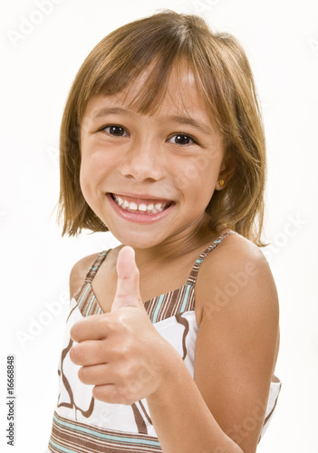 A young girl gives a smiling thumbs up