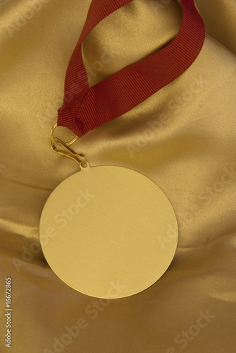 Gold medal on shiny golden cloth