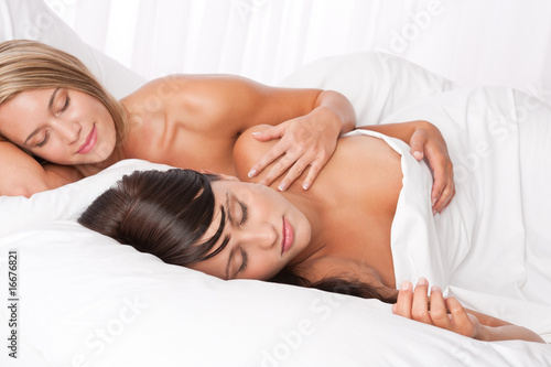 Blond woman and brunette sleeping in white bed