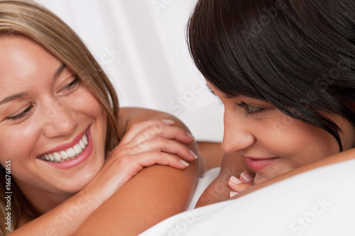 Portrait of two smiling women lying down in white bed