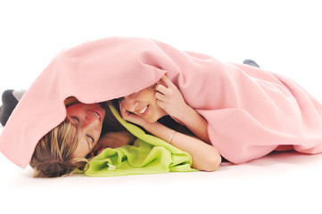 young girls under blanket smile