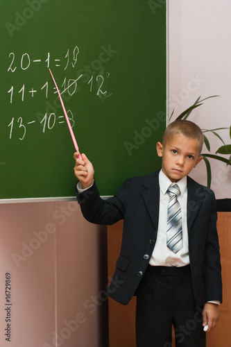 The schoolboy at a lesson of mathematics at a school board