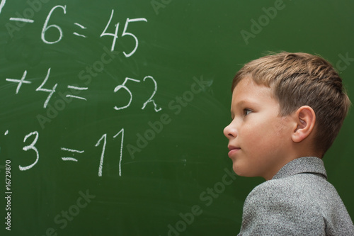 The schoolboy solves examples at a mathematics lesson
