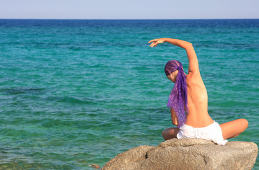 woman meditating in the afternoon by the sea in Greece