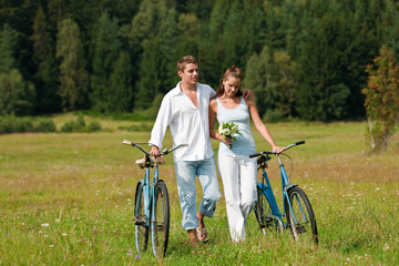 Romantic couple walking with old-fashioned bike