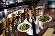 Hispanic waitress in restaurant serving salad plates