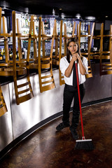 Hispanic bartender sweeping closed bar area
