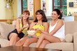 Three girls watching TV and eating popcorn