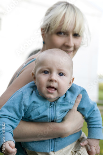 happy blond mother holding  her smiling baby