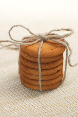 stacked ginger cookies tied by jute string on hessian background