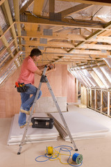 Electrician using meter on ladder in attic under construction