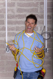 Laughing man entangled in electrical cable
