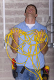 Frustrated man holding tangled electrical cable