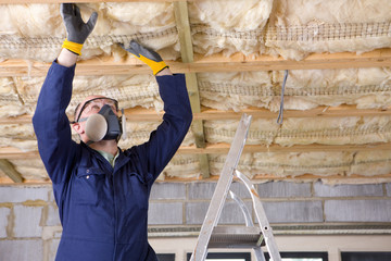 Man in coveralls and protective mask installing ceiling insulation