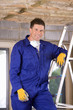 Smiling man in coveralls standing on ladder under ceiling insulation