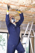 Man wearing protective mask and installing ceiling insulation