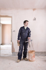 Man mixing plaster in house under construction