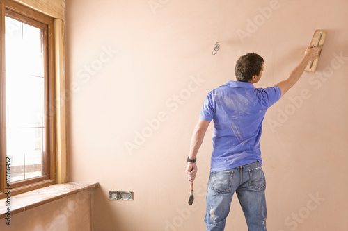 Man plastering wall in house