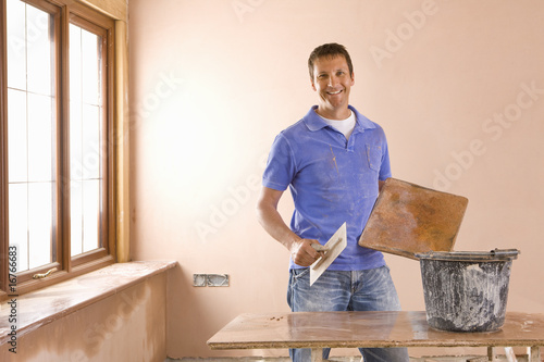 Smiling man holding trowel next to bucket of plaster