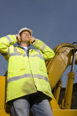 Construction worker wearing ear protectors and reflective clothing