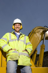Smiling construction worker wearing ear protectors and reflective clothing
