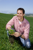 Smiling farmer examining young wheat crop