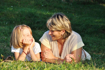 Child with mother, happiness on green meadow in summer time
