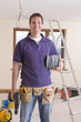 Smiling electrician holding cable spool and drill