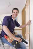 Smiling electrician holding drill and outlet on wall