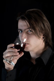 Handsome pale vampire with blue eyes drinking wine or blood poster