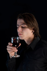 Handsome vampire with glass of wine or blood
