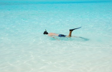 Young man snorkeling in Maldives (blue ocean water)