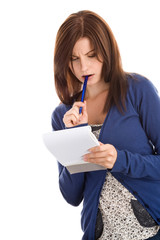 Young woman does records by pen in notepad thinking