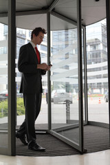 young caucasian businessman at office revolving door with cellph